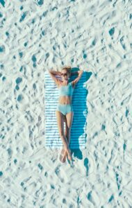 woman lying on sand with towel during daytime