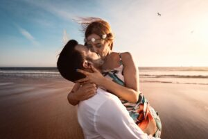 man and woman kissing on beach