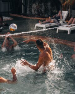 man in swimming pool playing volleyball during daytime